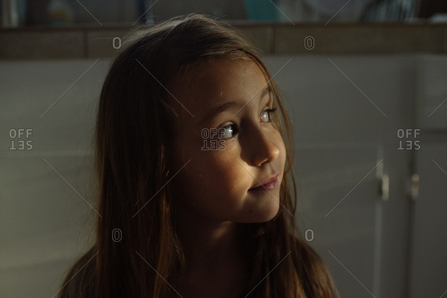 Girl standing in a kitchen glancing away