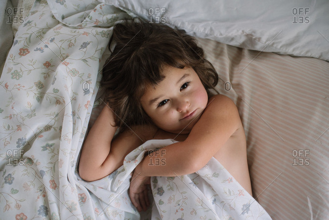 Little girl wrapped in sheets on a bed