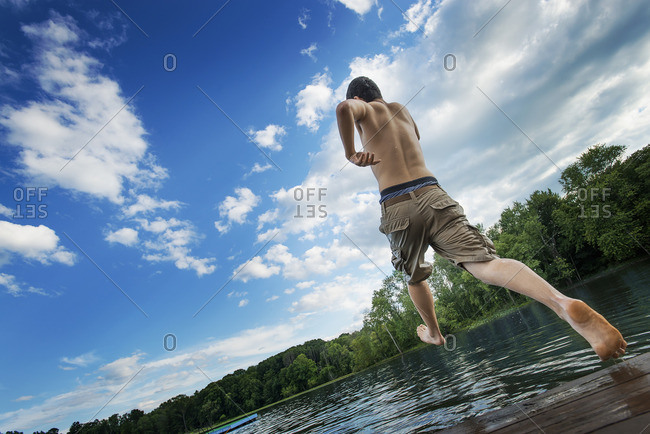 A boy taking a running jump into a calm pool of water, from a wooden jetty