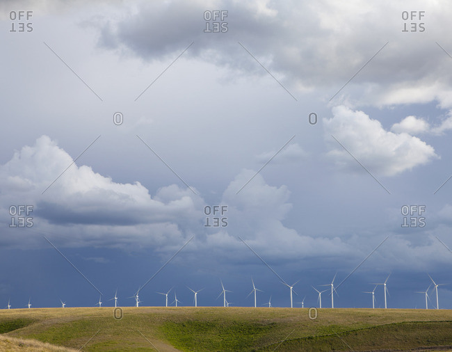 A line of wind turbines on a ridge, against a stormy sky