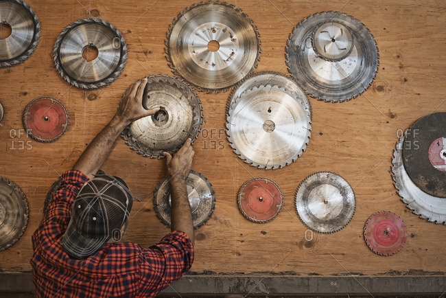 A reclaimed lumber workshop A man reaching up to a storage board for circular saw blades to replace a blade
