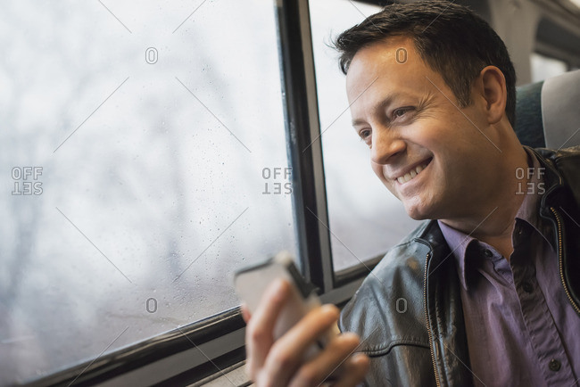 A mature man sitting at a window seat on a train, holding his mobile phone Smiling and looking in the distance