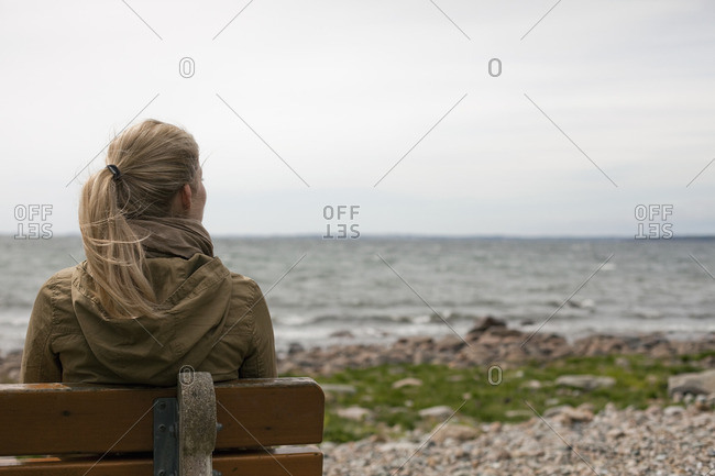 A woman with long blonde hair wearing a brown hooded coat, seated on a bench looking out to sea