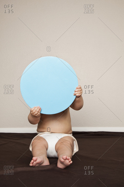 A young 8 month old baby boy wearing cloth diapers, hiding behind a large blue disc