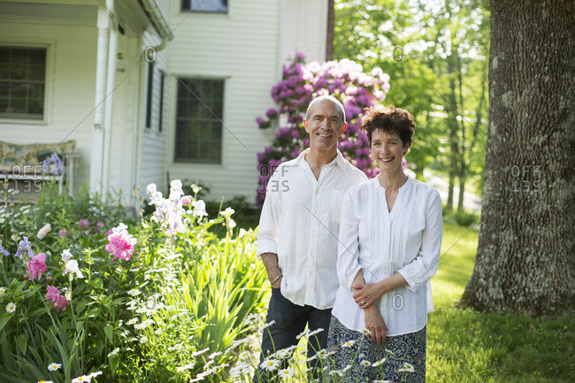A mature couple in white shirts standing together among flowers