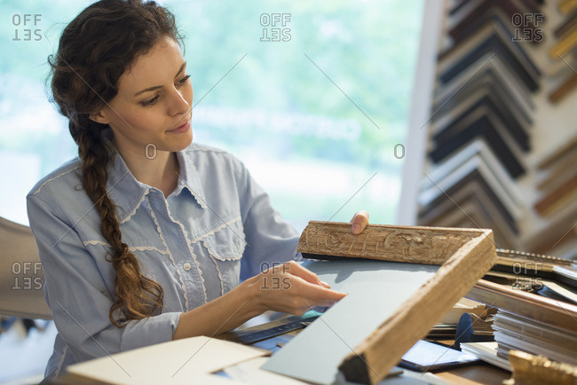 A woman in a picture framer's workshop, choosing frames and cardboard mounts Surrounded by samples