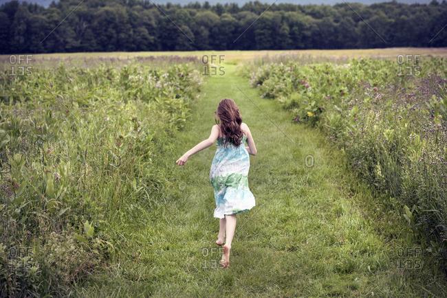 A girl running through a meadow in summer