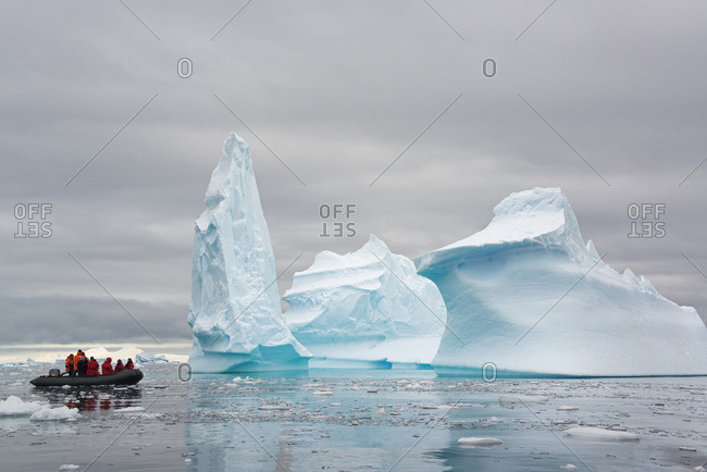 People in small inflatable zodiac rib boats passing towering sculpted icebergs on the calm water around small islands of the Antarctic Peninsula
