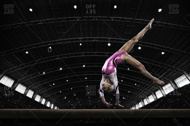 A young woman gymnast performing on the beam, balancing on her hands on a narrow piece of apparatus