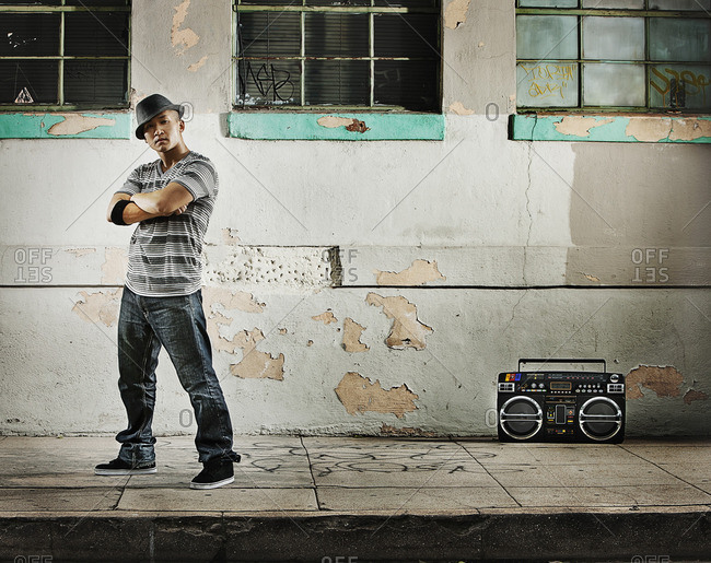 A young man, a breakdance performer with a boombox on the street of a city