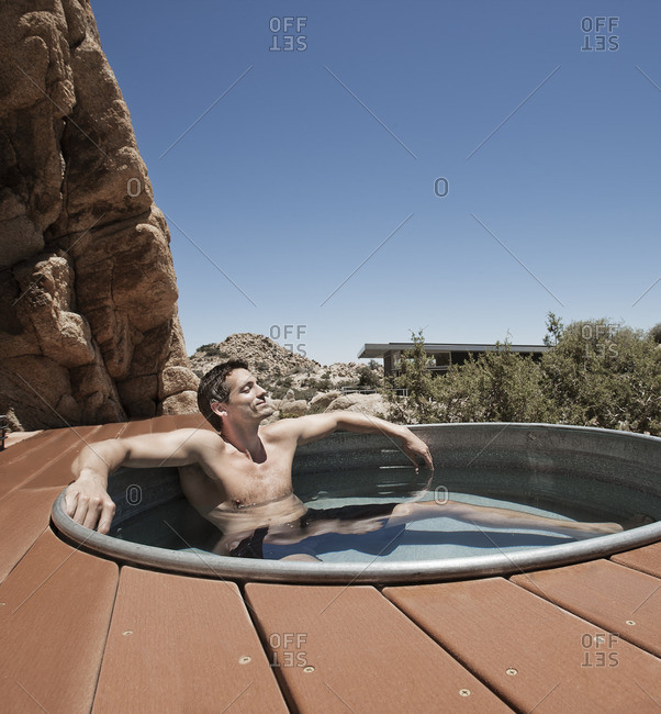 A man on the terrace of an eco home, a low impact house in the desert landscape, in a sunken hot tub