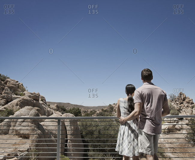 A man and woman on the terrace of an eco house, looking over the rocky landscape
