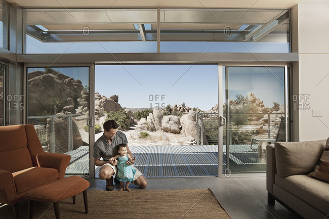 A man and a young child in an ecohouse, a home with large glass walls and view out over the rocky landscape