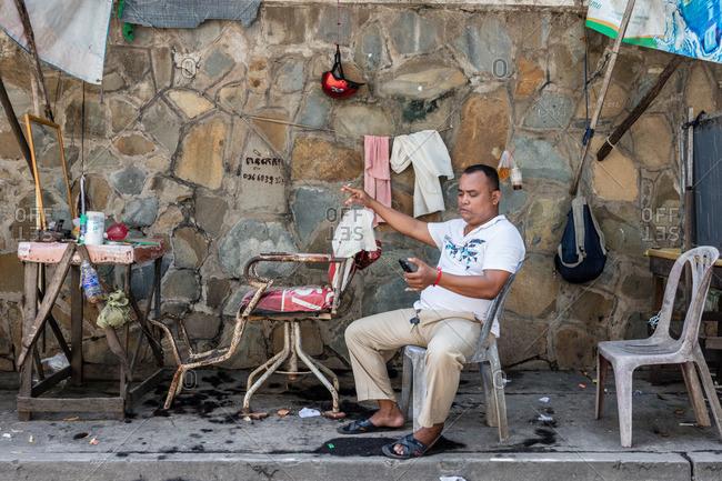 Cambodia - November 10, 2016: Street barber on his phone