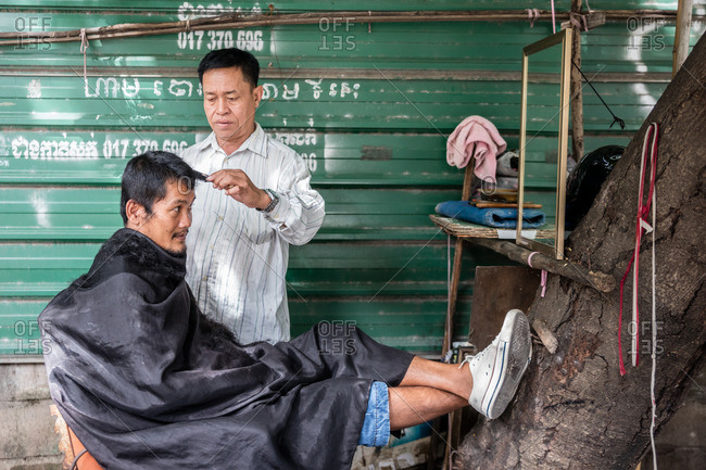 Cambodia - November 10, 2016: Man getting haircut from outdoor barber