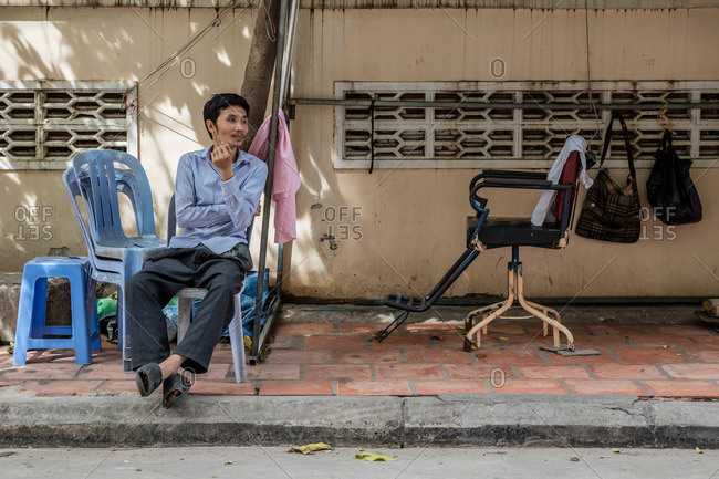 Cambodia - November 11, 2016: Sidewalk barber sitting outside