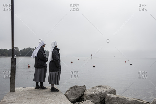 Two nuns standing on a shore