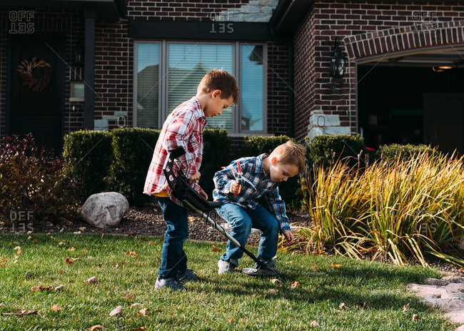Two boys using a metal detector to search their yard