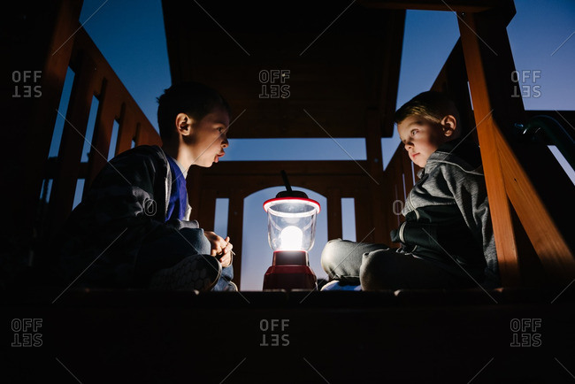 Two boys telling stories around a camping lantern