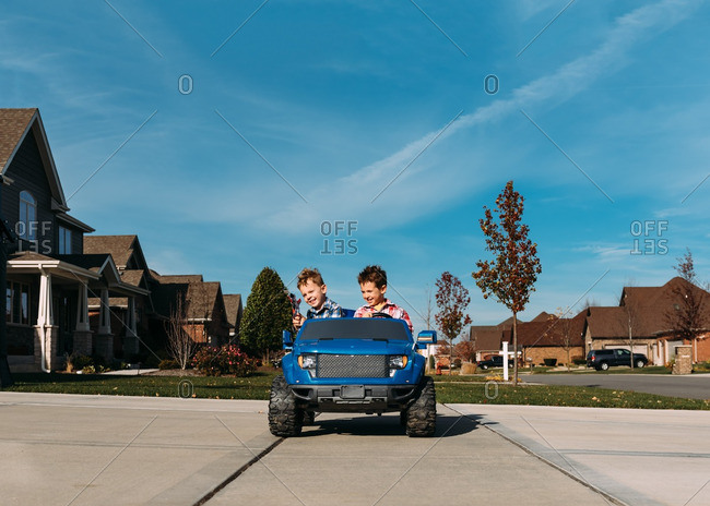 Boys riding a motorized toy truck in a driveway