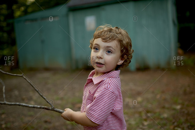 Curly haired boy holding a branch