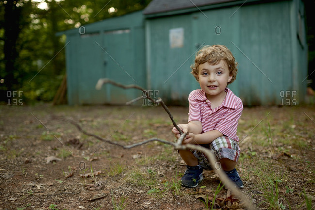 A curly haired boy holding a branch
