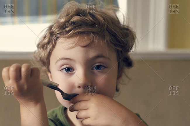 Curly haired boy eating with spoon