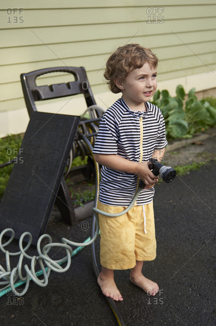 Boy with hose nozzle standing outside