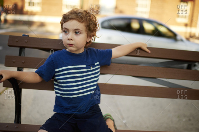 Boy on city bench looking away