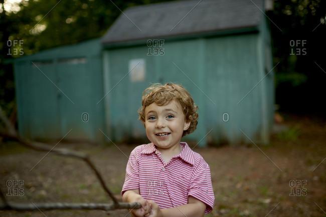 Smiling boy holding a stick