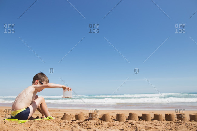 Boy building a row of sand castles on a beach