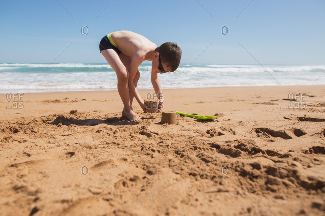 Boy playing in the sand on a beach