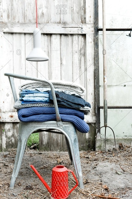 Clothes and blankets on metal chair