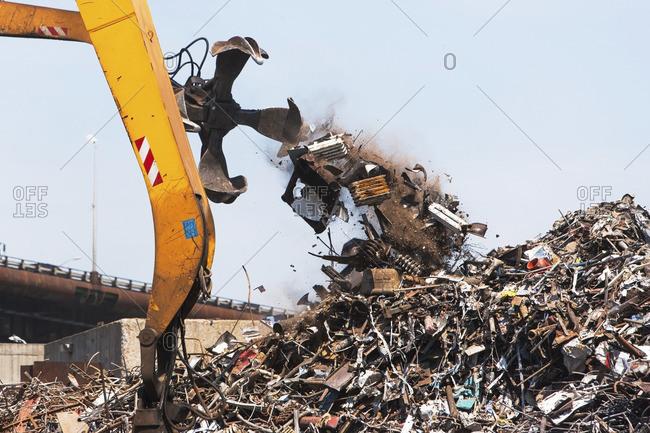 Crane and heap of scrap in junkyard
