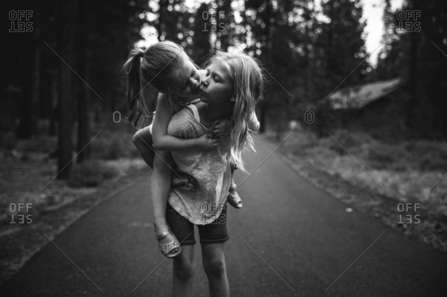 Girl giving her little sister a piggyback ride and a kiss
