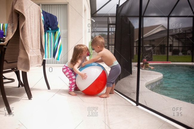 Twin toddlers fighting over a beach ball by a pool