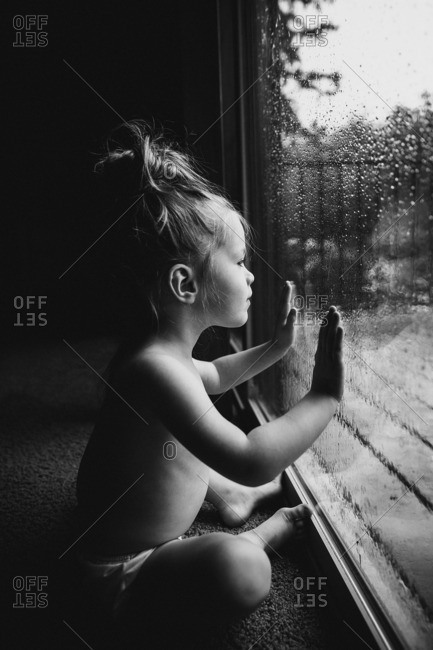 Toddler girl looking out a window on a rainy day