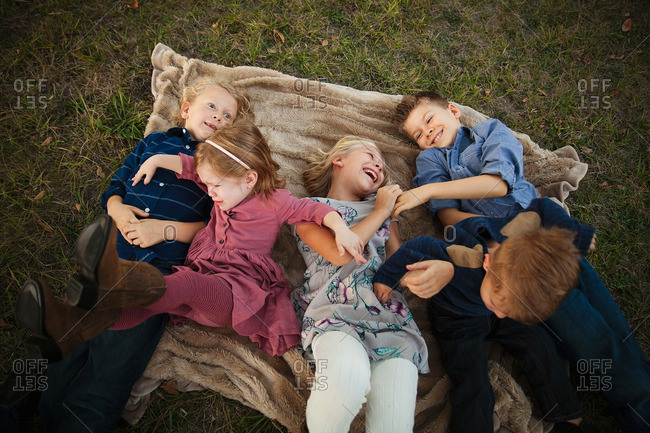 Siblings lying together laughing on a blanket with little sister upset
