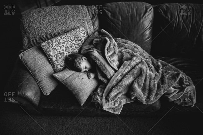 Toddler boy napping on a sofa wrapped in a furry blanket