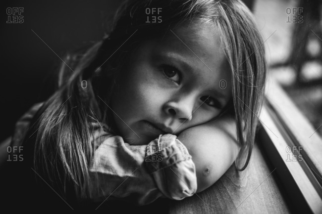 Toddler girl resting her head on a windowsill in black and white