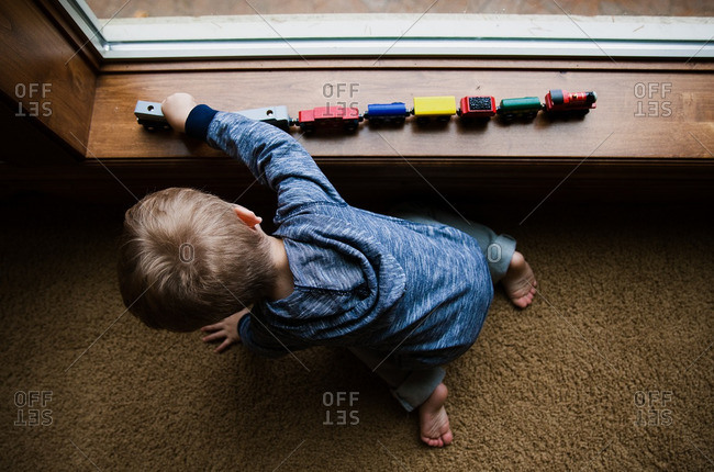 Toddler boy playing with toy train on a windowsill