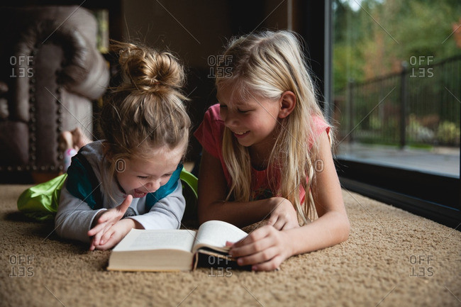 Girl reading a book to her little sister