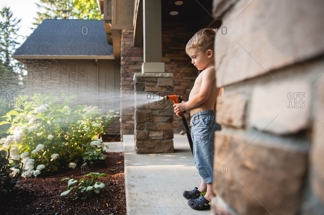 Toddler boy watering plants in the front yard
