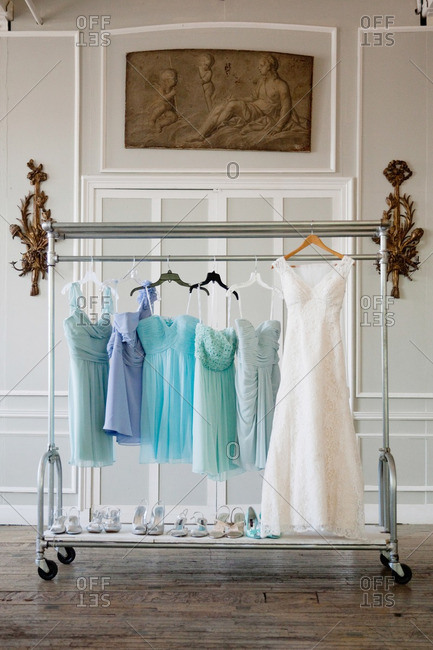 Bride and bridesmaid dresses hanging on a racks with shoes