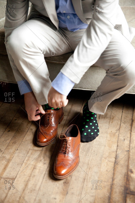Groom putting his shoes on before wedding