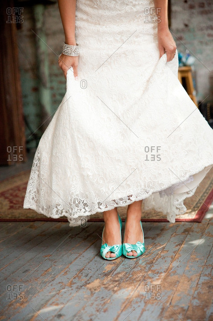 Bride lifting her dress to show of her teal peep-toe pumps