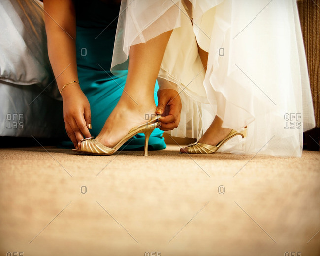 Bridesmaid helping bride put on her peep-toe pumps