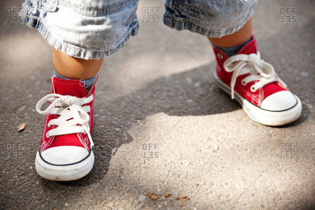 Close up of toddler boys feet in red sneakers