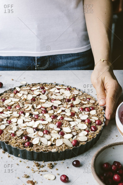 Woman holding a cranberry almond tart ready to be baked