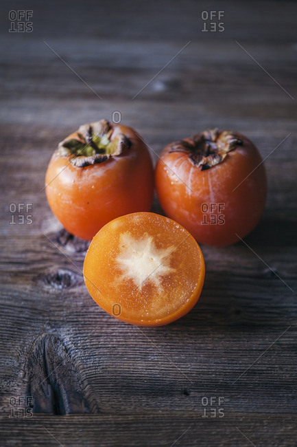 Halved and whole persimmons on a rustic wooden table